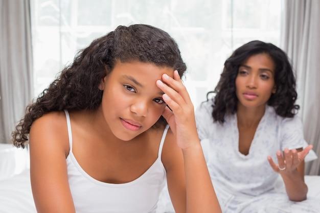 Mãe e filha tendo um argumento na cama