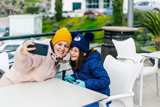Mãe e filha tirando uma selfie em um terraço ao ar livre
