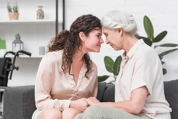Mãe e filha tocando cabeças juntas, segurando a mão do outro
