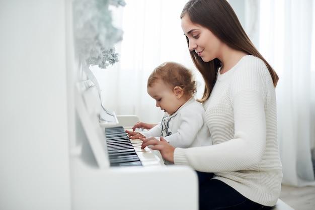 Mãe e filha tocando piano branco, close-up wiew