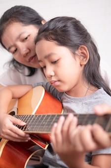Mãe e filha tocar violão