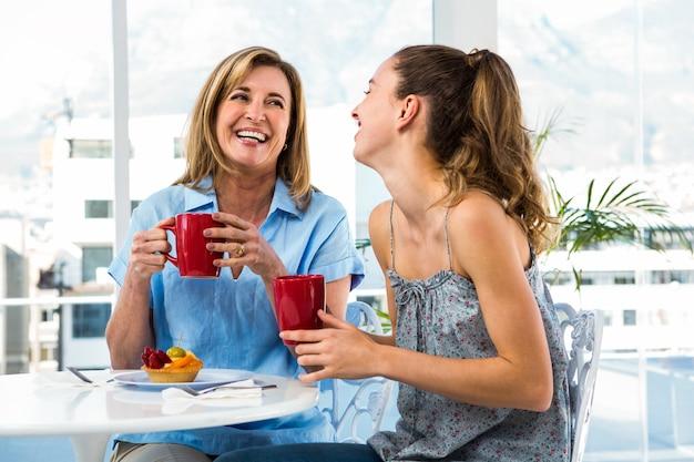 Mãe e filha tomam café da manhã em casa na cozinha