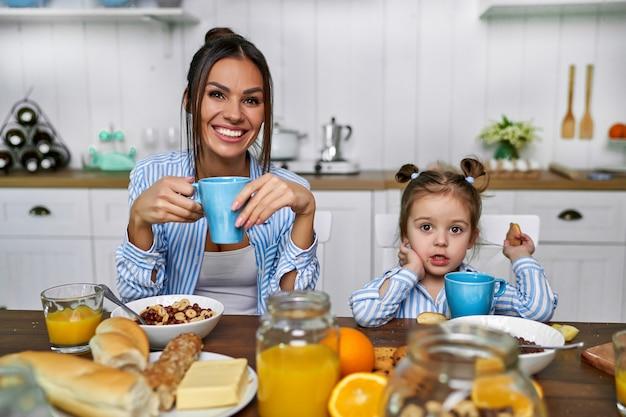 Mãe e filha tomam café da manhã em casa