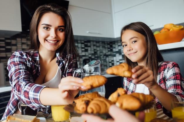 Mãe e filha tomando café da manhã com croissant na mesa