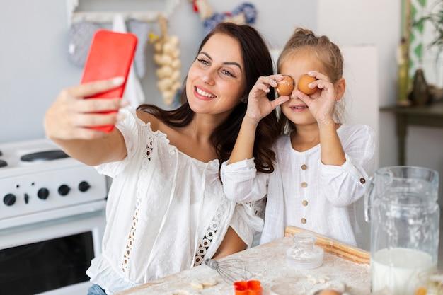 Mãe e filha tomando selfie com olhos de ovo