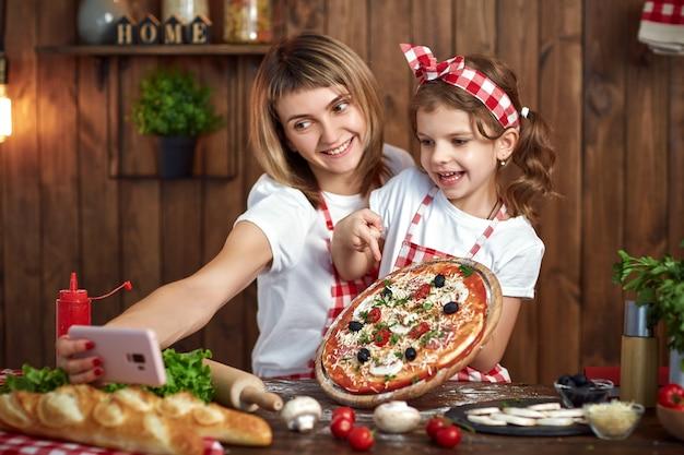 Mãe e filha tomando selfie com pizza no smartphone