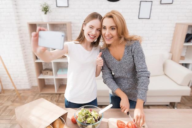 Mãe e filha tomando selfie na cozinha.
