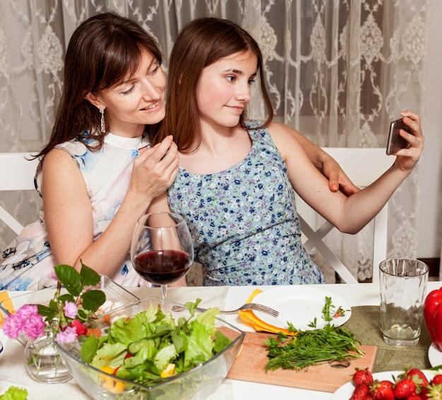 Mãe e filha tomando selfie na mesa de jantar