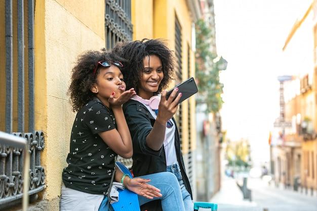 Mãe e filha tomando um selfie juntos