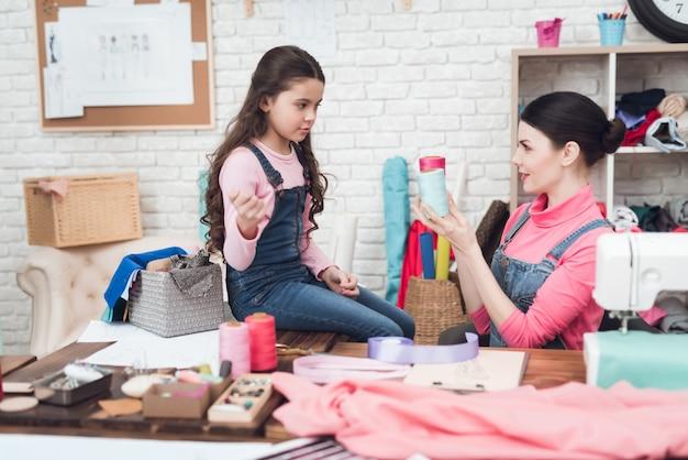 Mãe e filha trabalham juntos na oficina de costura.