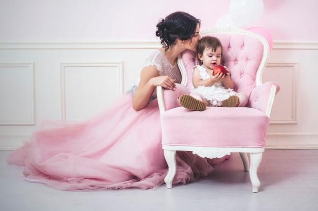Mãe e filha um lindo e feliz interior rosa com uma cadeira vintage e bolas em lindos vestidos de férias