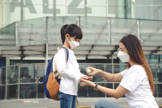 Mãe e filha usam máscara durante surto de coronavírus desinfetante para as mãos