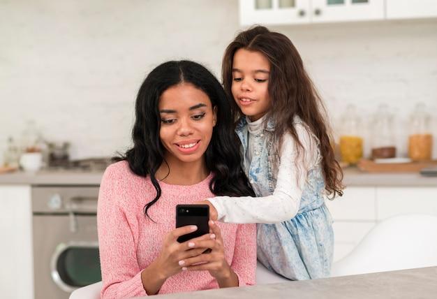 Mãe e filha usando celular