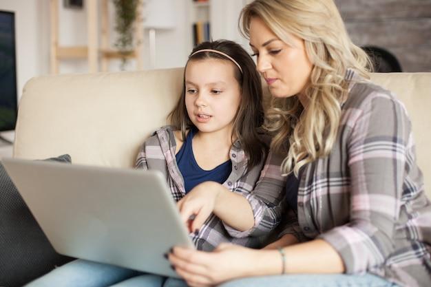 Mãe e filha usando laptop com tecnologia sem fio para navegar na internet.