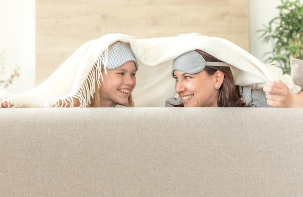 Mãe e filha usando máscara de dormir se divertindo no sofá