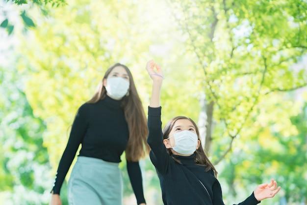 Mãe e filha usando máscaras e brincando no parque
