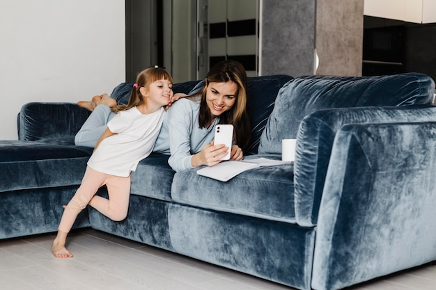 Mãe e filha usando o celular juntas
