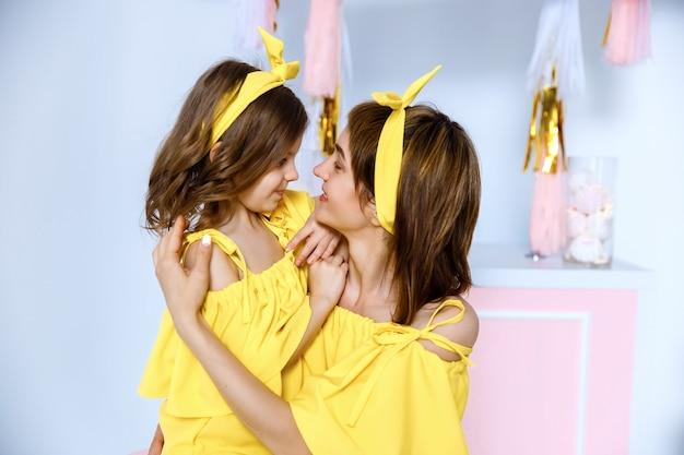 Mãe e filha usando o mesmo vestido amarelo.