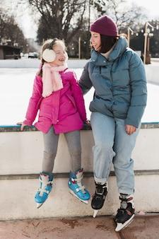 Mãe e filha usando patins de gelo