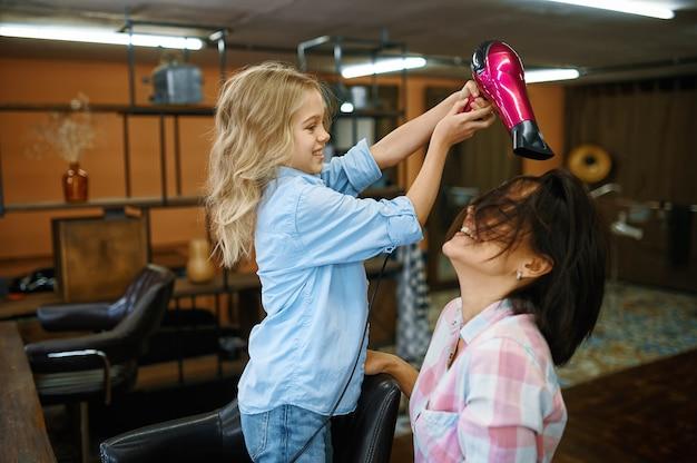 Mãe e filha usando secador de cabelo em salão de maquiagem