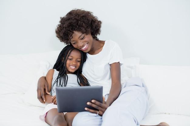 Mãe e filha usando tablet digital no quarto