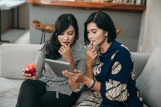Mãe e filha usando tablet surpreso