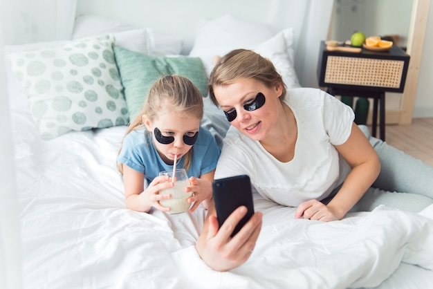 Mãe e filha, usando tapa-olhos, bebem smoothie e tomam selfie ou videochamada de spa e procedimentos de cuidados com o corpo