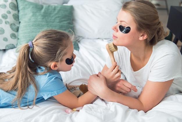 Mãe e filha usando tapa-olhos e escova para cuidados com a pele do rosto, spa e processo de cuidados com o corpo