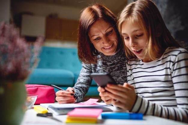 Mãe e filha usando telefone inteligente