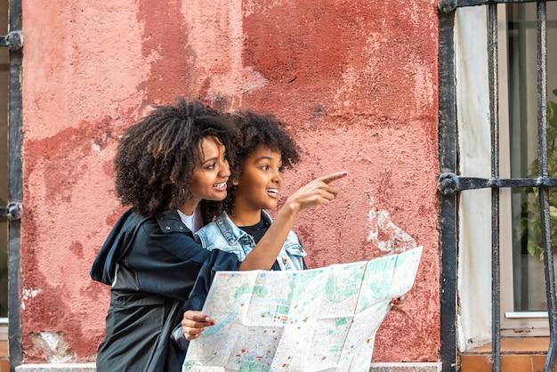 Mãe e filha usando um mapa na rua.