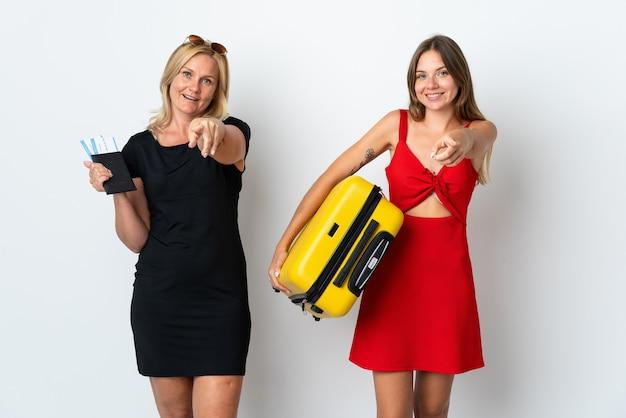 Mãe e filha vão viajar isoladas em uma parede branca apontando o dedo para você com uma expressão confiante