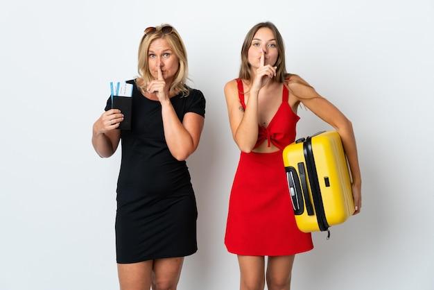 Mãe e filha vão viajar isoladas na parede branca mostrando sinal de silêncio gesto colocando o dedo na boca