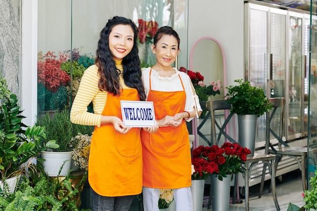Mãe e filha vietnamitas sorridentes com aventais laranja abrindo floricultura