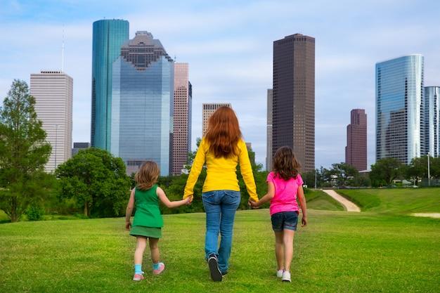 Mãe e filhas andando de mãos dadas no horizonte da cidade