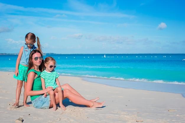 Mãe e filhas, aproveitando o tempo na praia tropical