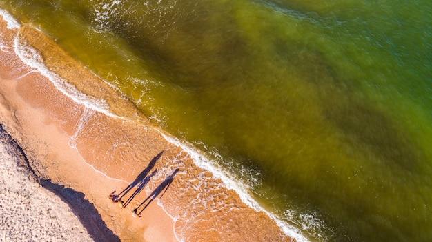 Mãe e filhas caminham através das ondas à beira-mar, câmera drone