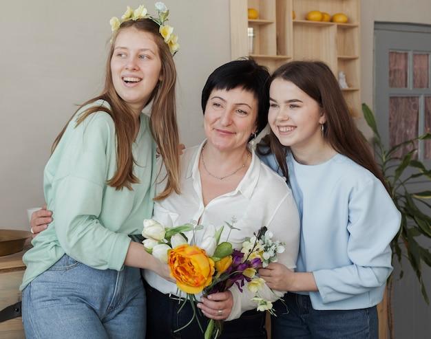Mãe e filhas com buquê de flores