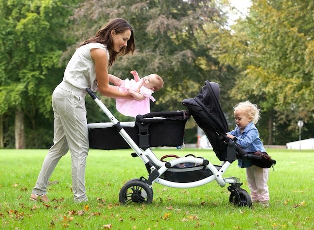 Mãe e filhas, com, pram, ao ar livre