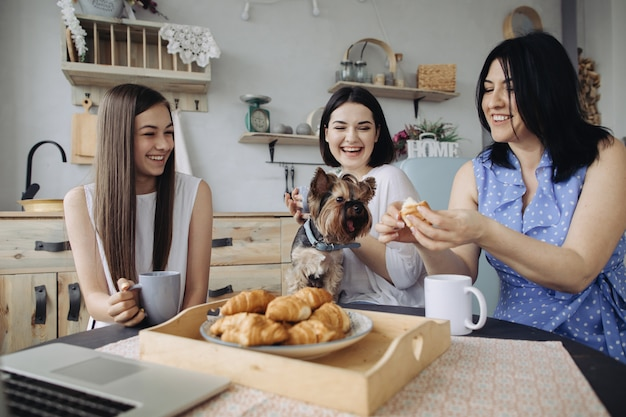 Mãe e filhas conversando e comendo croissants na cozinha