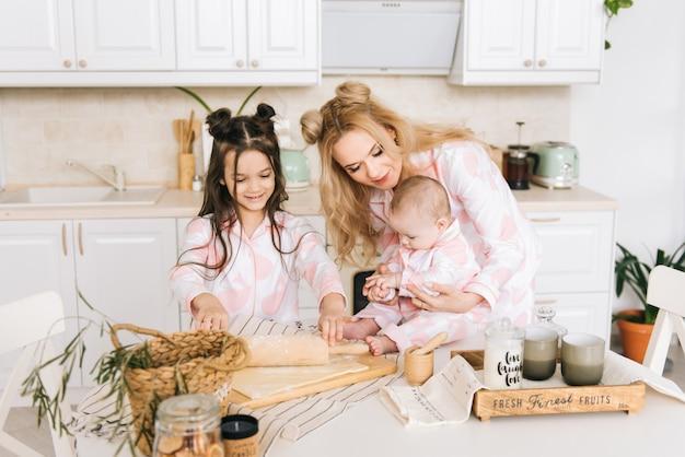 Mãe e filhas cozinhando na cozinha