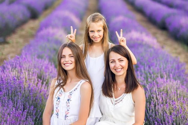 Mãe e filhas em um campo de lavanda. foto de verão nas cores roxas.