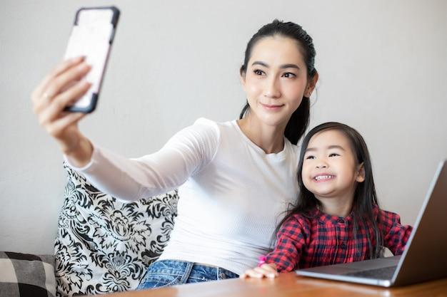 Mãe e filhas estão tirando selfies e rindo e sorrindo felizes