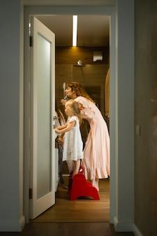 Mãe e filhas fazem maquiagem no banheiro, aplique batom na frente do espelho.