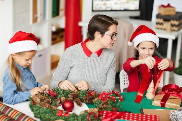 Mãe e filhas felizes decorando a guirlanda de natal