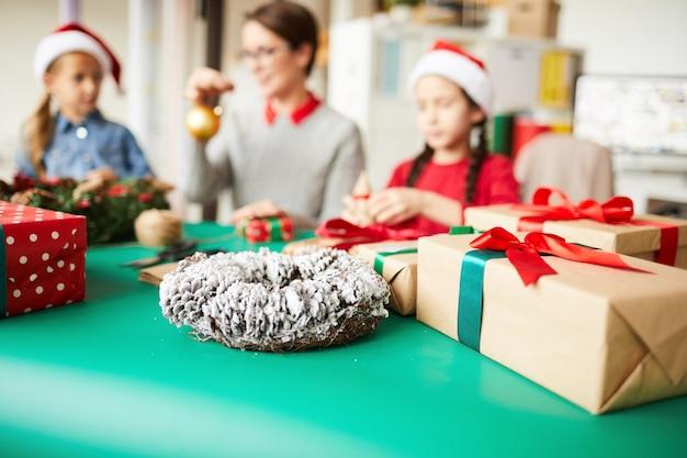 Mãe e filhas felizes embrulhando presentes de natal