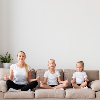 Mãe e filhas meditando no sofá em casa
