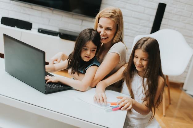 Mãe e filhas na sala de surf no laptop