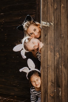 Mãe e filhas olhando por trás da porta