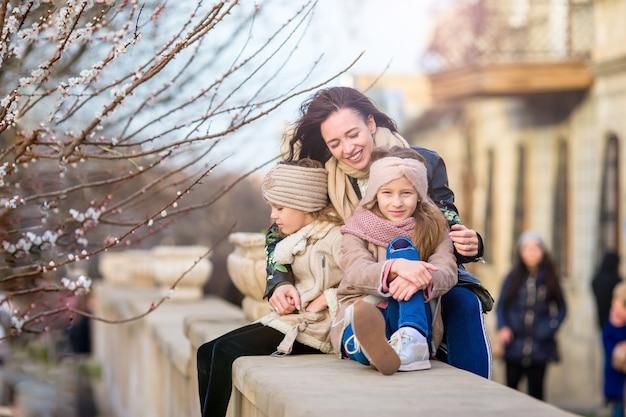 Mãe e filhas pequenas ao ar livre na cidade