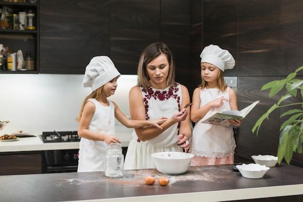 Mãe e filhas preparando comida na cozinha